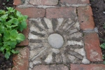 Paving panel with round pebble and broken roof tiles standing on edge